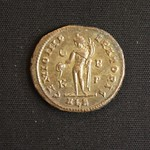 "<b>345 Reverse</b><br/> The person depicted on the reverse of this coin is a Genius, a representation of something divine, and often depicted as a naked man holding a plate and a cornucopia. The key around the edge reads ""GENIO IMPERATORI"" or ""Spirit of the Emperor,"" likely the emperor featured on the obverse, Maximian. The area below the image is called the exegis, and often contains a mint mark, allowing us to tell where the coin was minted. The ALE in the exegis indicates a minting origin of Alexandria.  Donated by Dr. Orlando ""Pip"" Qualley<a href=""http://farm5.static.flickr.com/4065/4352106744_c86c1b2265_o.jpg"" title=""High res"">∝</a>"