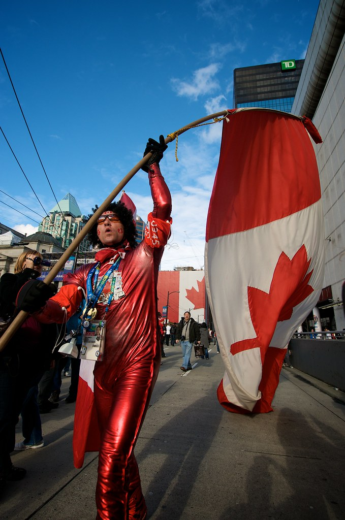 Man Carries Large Canadian Flag and Wears Onesie