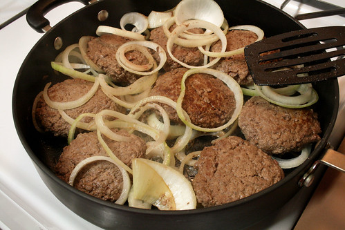 Cooking the onions and beef patties together.