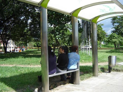 ESPERAN DE ESPALDAS EN PARADA DE BUS
