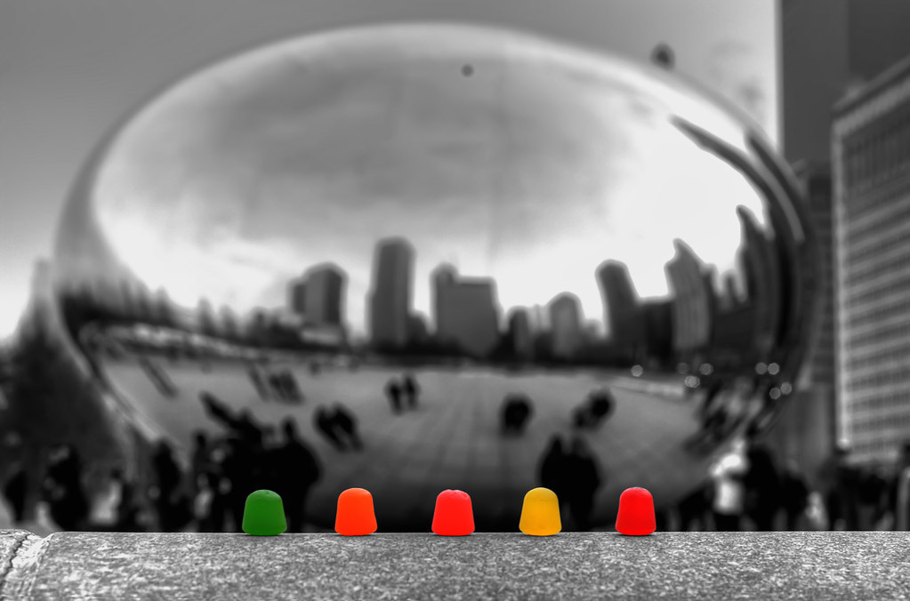 "A few candies laid out in front of ""The Bean"" aka Cloudgate in Millenium Park."