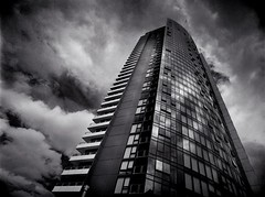 tipping point (mugley) Tags: city windows urban blackandwhite bw building tower 120 film glass lines architecture modern clouds rollei skyscraper mediumformat reflections concrete prime 645 apartments grain perspective dramatic australia melbourne wideangle victoria scan negative balconies epson docklands curve polarizer 6x45 vignetting r3 cloudporn mamiya645 urbanlandscape redfilter polariser blacksky 25a v700 cloudage keystoning victoriapoint mamiya645protl m645 rolleir3 35mmf35sekorn stadiumconcourse