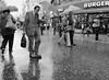One's company (Ian Brumpton) Tags: street urban blackandwhite bw london blancoynegro rain umbrella noiretblanc candid streetphotography monotone leicestersquare biancoenero londonist raintown londonstreetphotography justwalkingintherain lifeinslowmotion aimlessstrolling blackwhiteheartbeats onescompany