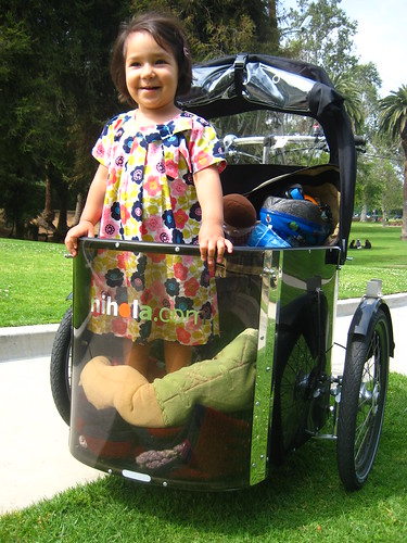 A young girl standing in stationary Nihola Family cargo bike.