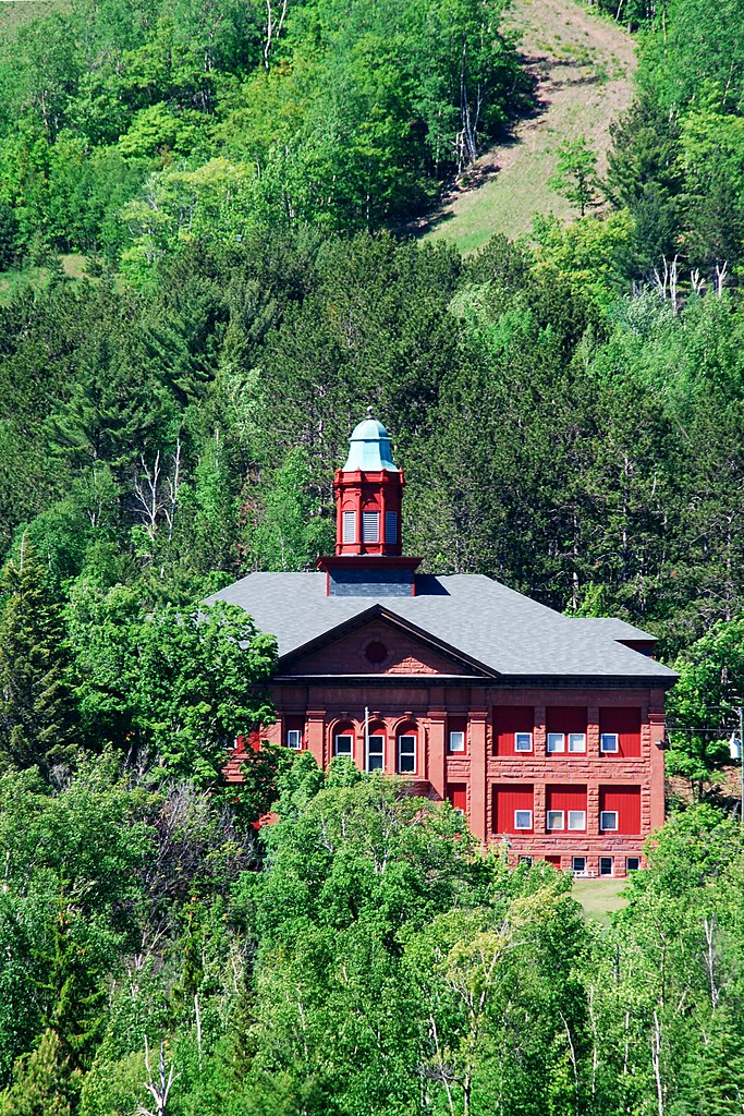 A red stone building nestled in trees.