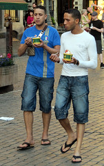 Taste Testers (Legin_2009) Tags: road street food man male men walking outside outdoors couple europe european eating pavement walk sandals duo pair jeans eat arab icecream flipflops jersey males shorts slippers mnner hombres mec  mecs  threequarter gason    hommes homens