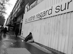 Ici, votre regard... (anw.fr) Tags: city blackandwhite bw paris rain contrast homeless poor streetphotography pluie nb advertisement rainy irony contraste ironic society rue sdf ricoh ville socit sarcastic pauvre ironie pluvieux grd sansdomicile ironique sansdomicilefixe affichepublicitaire sarcastique
