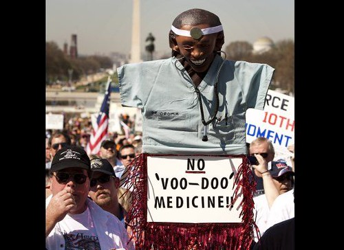 tea party protesters holding a racist sign at a rally