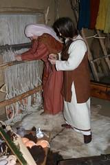 Stiftsfrau Harlindia und Hallveig im Haus des Tuchhändlers an dem Gewichtswebstuhl in Haithabu - Museumsfreifläche Wikinger Museum Haithabu WHH 04-04-2010