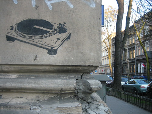 graffiti of a turntable, painted onto the side of a grey concrete building ornamentation