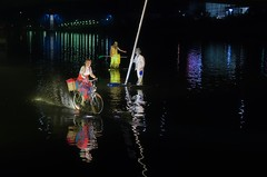Nor rain, nor snow, nor rivers wide... (Jumpin'Jack) Tags: woman dressed ina funny striped baggy pants skirt suspenders riding bicycle bike ona river water splashing inan arc behind wheels garbage collector thrashman holding broom thrash bin can man wearing jacket coat leaning tilted street lamp pole lights reflection distortion theatre performance aqua forte drava festival lent maribor night shot