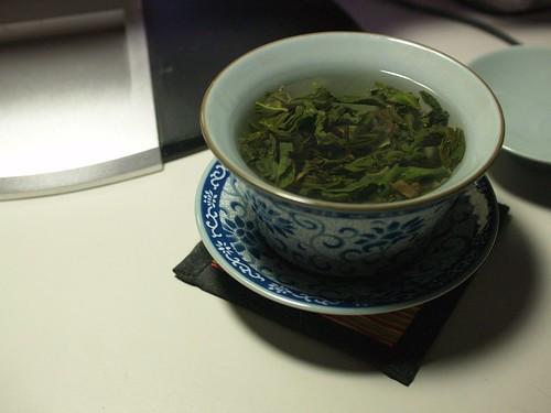 像個員外似的用蓋杯喝茶。
