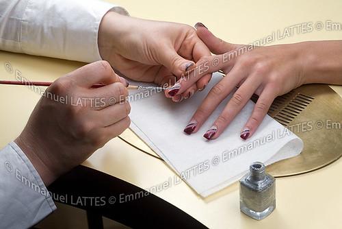 Décoration de faux ongles au pinceau.