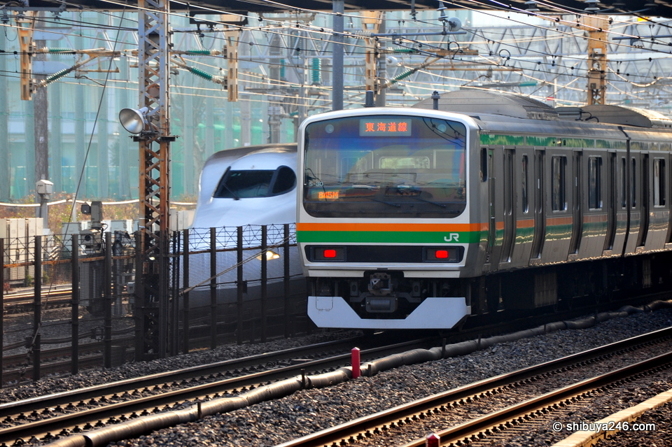 The Shinkansen takes a peak from behind the Tokaido Line. The old and the new. I can easily guess who will win this race.