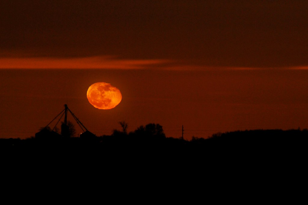 An orange moon rising, wavy, over farm buildings.
