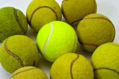 Brand new tennis ball among eight used ones