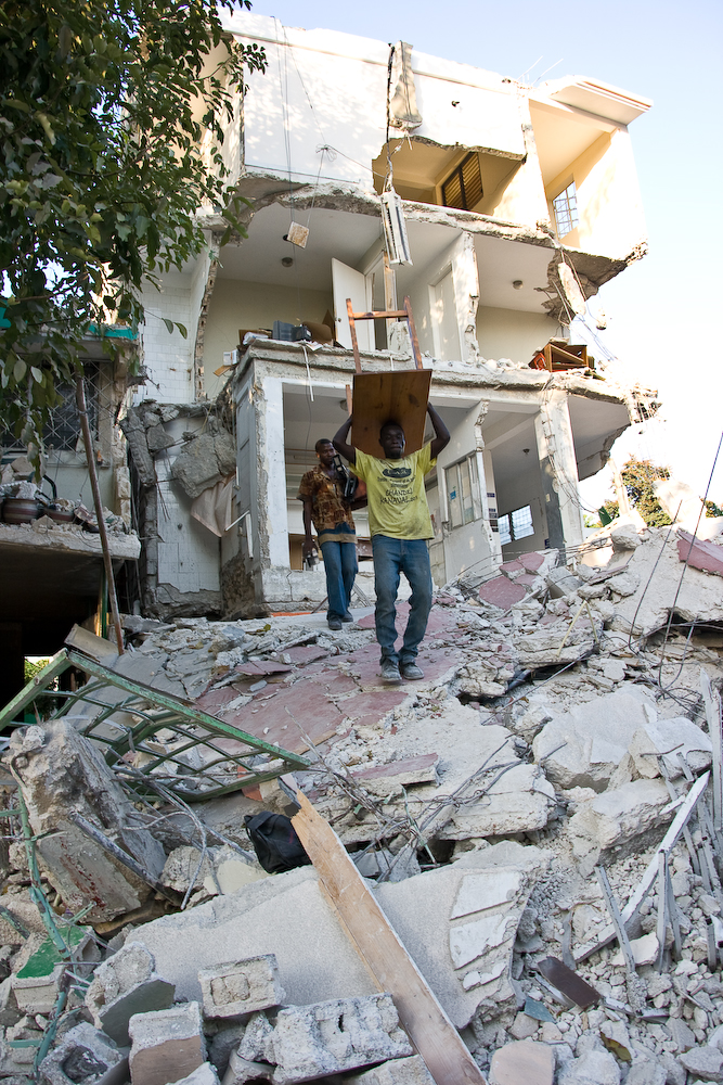 Men salvage furniture from an earthquake-damaged house in Port-au-Prince