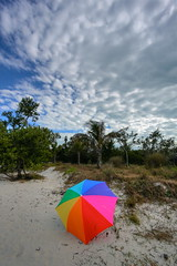 Lighthouse and Umbrella (TVGuy) Tags: trees sky lighthouse beach clouds umbrella island rainbow florida sanibel rtdgulf