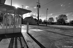 Thin Shade (Galen Lockwood) Tags: lighting bw sun house building tree glass clouds wire nikon downtown glow shine bright pavement michigan shade granite kalamazoo cracked waterdrain d300s telephonepull