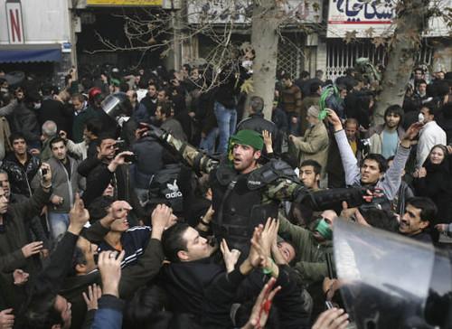 Polizist mit grünem Schal bei Protesten
