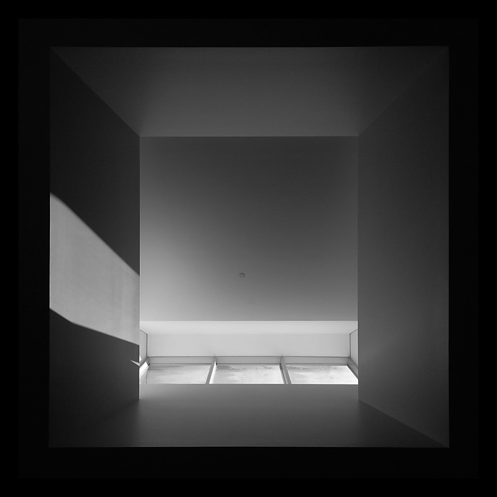 A black and white abstract composition, looking up at a skylight.