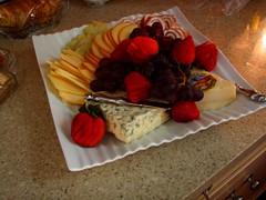 a sample plate of different cheeses and fruits with stawberries and grapes and crackers