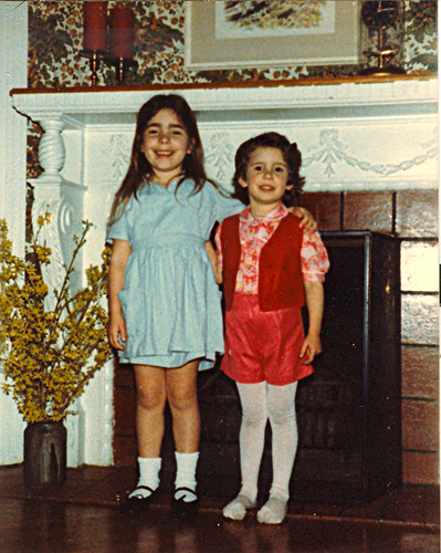 me and my older sister standing in front of the fireplace in the living room