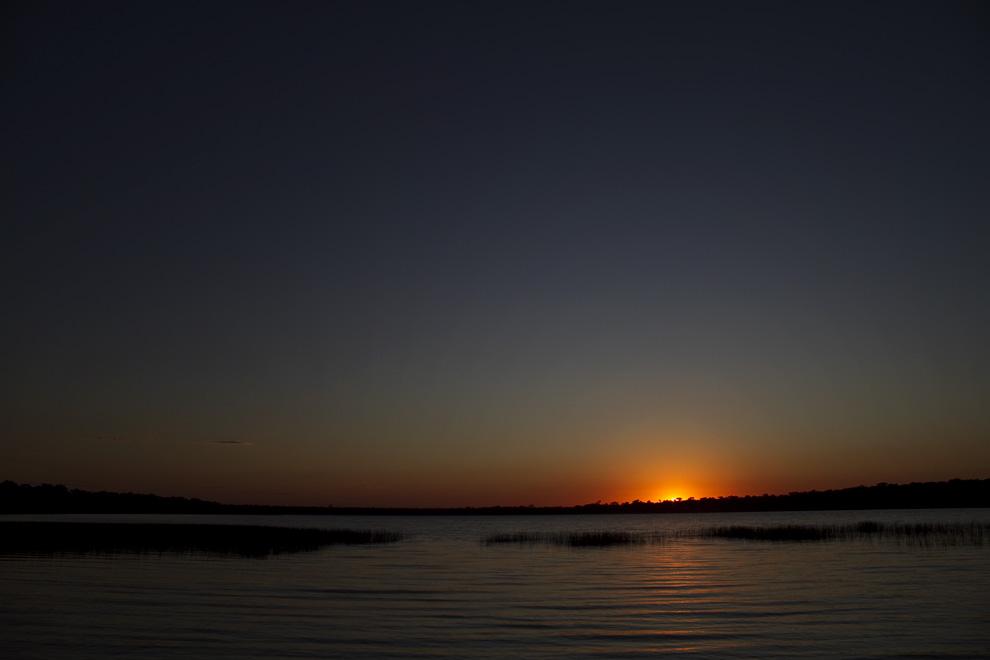 El sol da sus primeros rayos en el horizonte y baña de luz las transparentes aguas de la Laguna. (Santa Rosa del Aguaray, San Pedro, Paraguay - Tetsu Espósito)