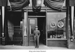 自分の店の前で写真を撮る男性