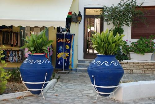 Stora blå krukor utanför en affär som säljer bland annat handukar med texten Samos