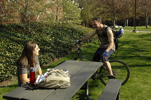 a male and female on college campus talking with each other on a sunny day