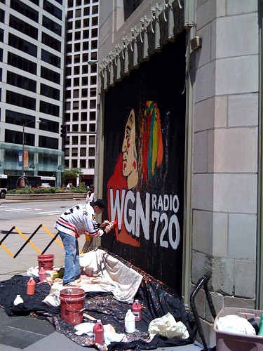 A Chicago Blackhawks logo is being painted on the WGN window at Tribune Tower
