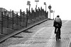 Cobblestone Climb (peterkelly) Tags: street bw signs canada man bike bicycle digital fence cyclist traffic quebec montreal hill canadian cobblestone riding stopsign northamerica uphill oldcity
