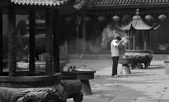Praying for time (Ruben Mascaró Photography) Tags: china blackandwhite bw white man black male canon temple candle shanghai smoke praying sneakers pot pots jeans burning tiles lanterns lantern jadebuddhatemple prc 30d peoplesrepublicofchina puxi incence canon30d canonefs1855mmf3556iiusm