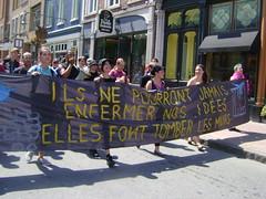 Cinq jeunes femmes, devant la marche sur la rue St-Jean, tiennent une banderole: Ils ne pourront jamais enfermer nos idées. Elles font tomber les murs.