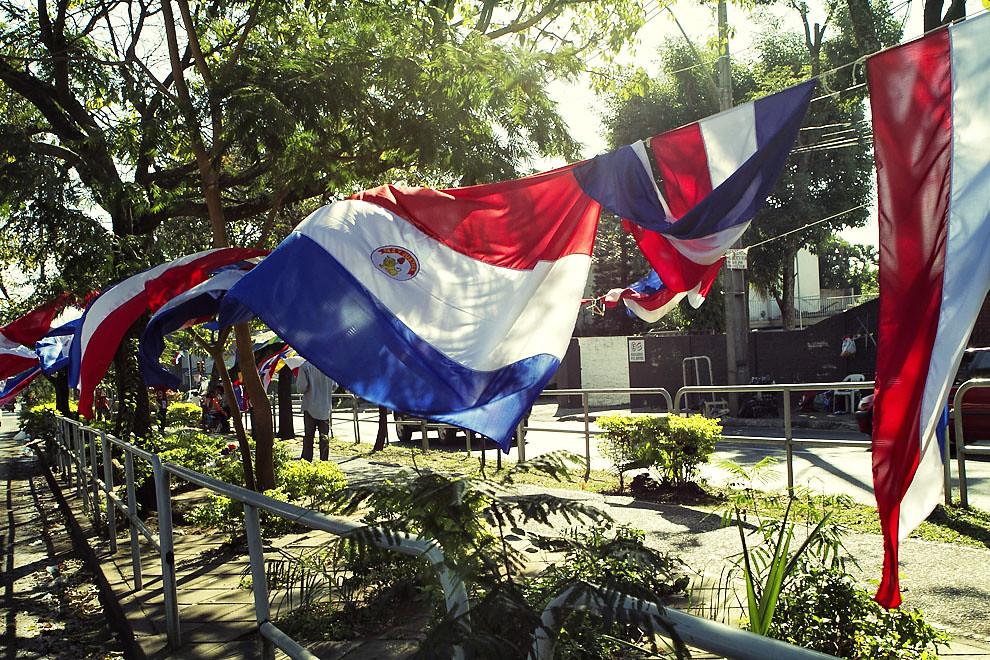 Banderas Paraguayas en venta flamean al viento en una concurrida avenida de Asunción. (Tetsu Espósito, Asunción, Paraguay)