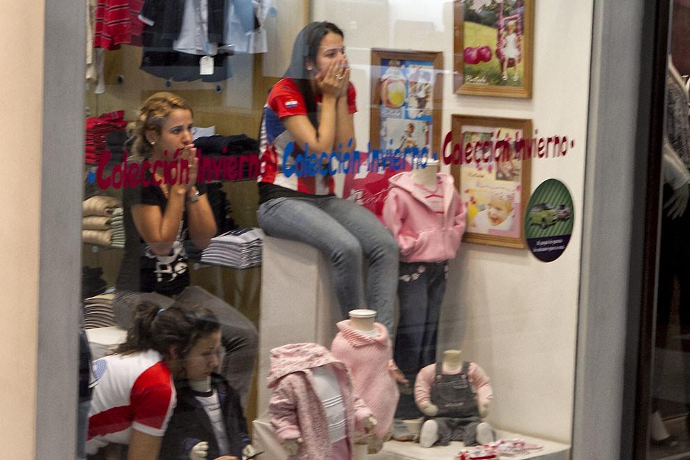 Tres chicas observan el encuentro de fubtol desde la vidriera de un shopping capitalino. (Tetsu Espósito, Asunción, Paraguay)