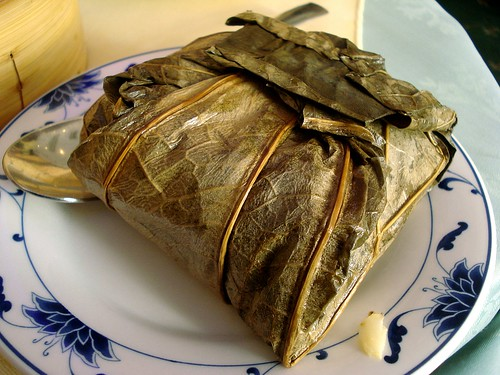 A neat, square, lotus leaf wrapped parcel sits on a plate waiting to be unwrapped.