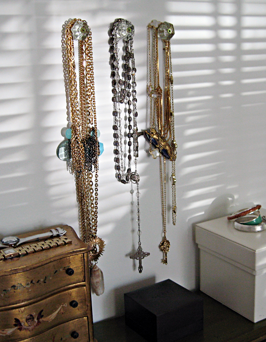 necklaces hanging from vintage glass knobs, how to organize jewelry necklaces bracelets earrings, hang necklaces on the wall, where to keep your jewelry