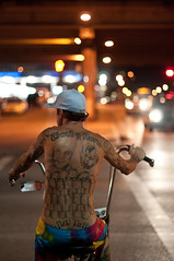 Tattooed Biker (christian.senger) Tags: road street city travel blue light red portrait people urban usa white man black car bike bicycle tattoo night digital america silver austin geotagged outdoors grey nikon texas dof hand bokeh availablelight gray cap saddle lightroom d300 christian_senger:year=2010