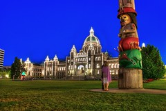 Tourists Reading the Plaque: Victoria British Columbia (Brandon Godfrey) Tags: flowers blue trees roof summer sky white canada color colour building tree fountain grass architecture buildings lights twilight colorful bc britishcolumbia sony capital lawn parliament totem victoria tourist canadian tourists pole vancouverisland hour dome copper pacificnorthwest northamerica colourful dslr legislature hdr highdynamicrange 2010 1898 a300 photomatix tonemapped tonemapping