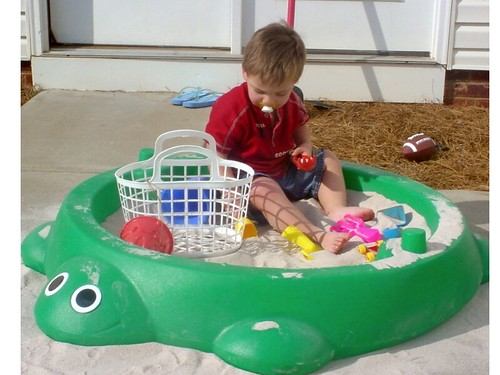 Kid in sandbox with toys