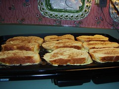 nine slices of bread cooking on the griddle with cinnamon on top