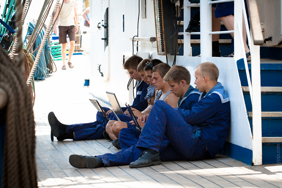Sailors in uniform sitting on a deck and using laptop computers