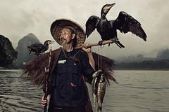 A Chinese fisherman with his two cormorants (Glenn Meling) Tags: china bird birds canon fisherman bravo smoke yangshou comorant imagepoetry bej thebestofday gnneniyisi absolutegoldenmasterpiece