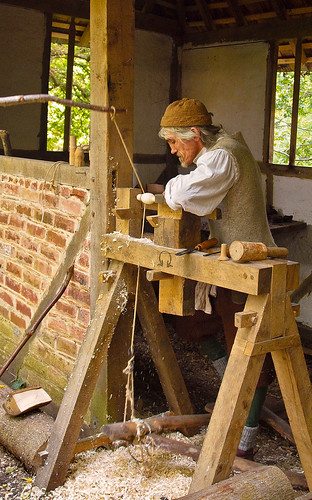 Tom the wood turner uses a pole lathe to fashion a wooden spoon in Little Woodham Living History Village