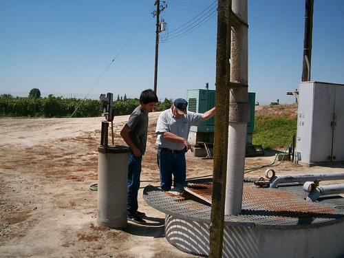Jerry Mendoza, student reporter (left); and Dave McIntyre, District Manager for Caruthers CSD inspecting the lift station at the wastewater treatment plant.