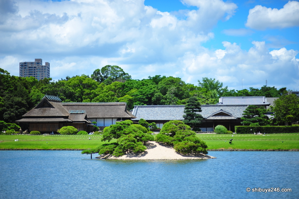The pond and buildings in a natural setting, with Okayama city close by
