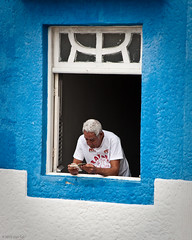At the Window (Ugo Cei) Tags: old travel blue brazil white man window southamerica brasil reading book nikon colorful br painted elderly aged pe olinda 2010 nordeste d90 nikond90