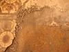 La piastrella arancione che riemerge da sotto gli strati